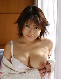 Sexy Asian model in lingerie is happily showing her big tits and hot ass